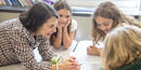 Three young girls have a conversation with a female mentor.