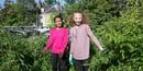 Two tween girls work together in an urban garden.