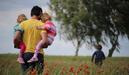 A dad carries his two daughters outside in a field.
