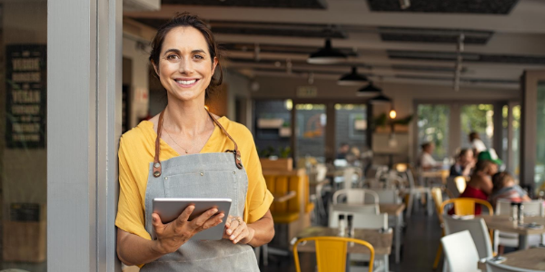smiling small business owner holding iPad
