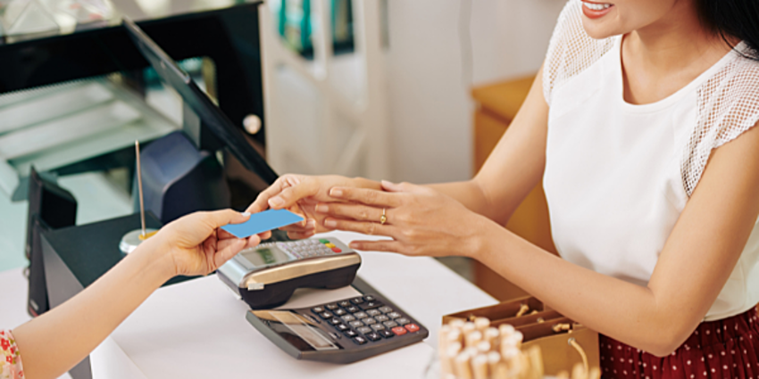woman handing credit card to cashier for payment