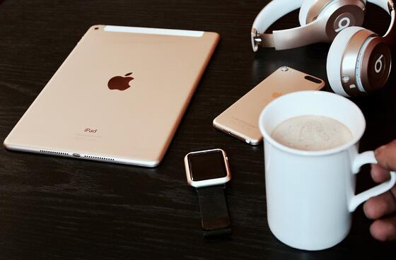 An Apple iPad, watch, and iPhone sit on a table beside Beats headphones and a cup of coffee