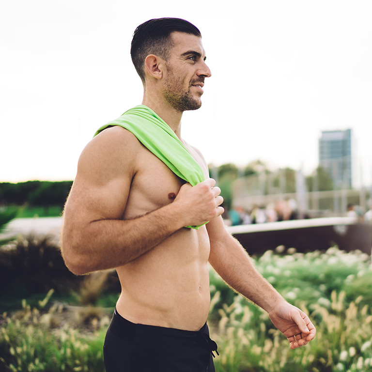 Muscular man with defined abs and biceps that are possible with CoolSculpting and CoolTone