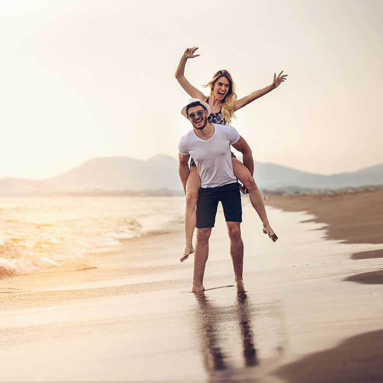 Young active couple on the beach illustrating the non-invasive nature of CoolSculpting with no down time (unlike liposuction)