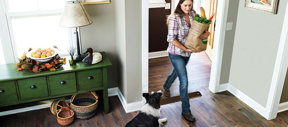 dog owner walking in with groceries with front door open