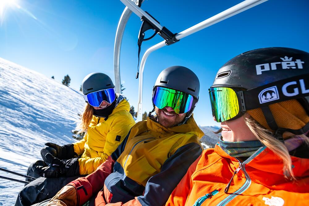 skiers on a chairlift in Vail, CO