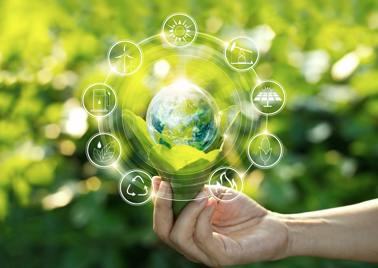 A hand holds a planet earth, surrounded by symbols of green energy