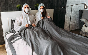 couple in bed wearing face masks