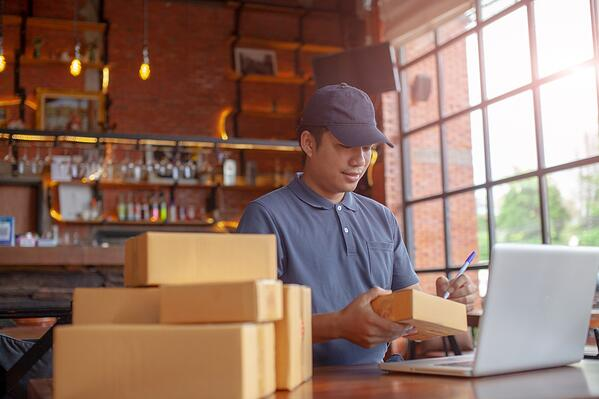 man at work with laptop and packages