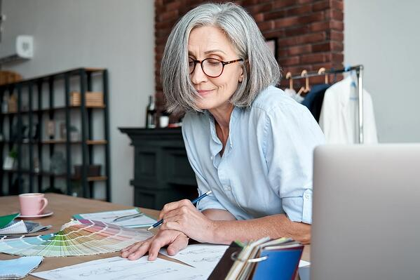 retired woman looking over paint palettes at table