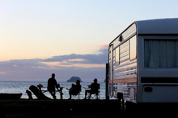 three sitting by camper watching sunset