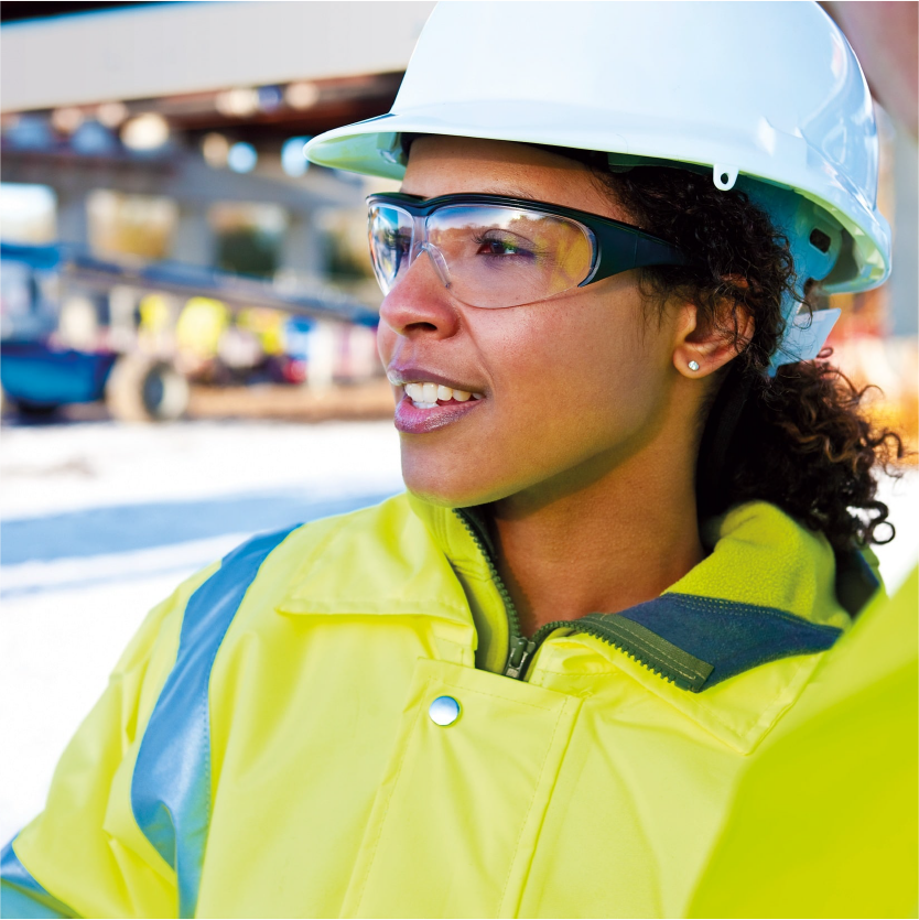 A health and safety worker wears protective clothing supplied by Bunzl, including hard hat, high visibility jacket and safety glasses-min