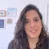 Foto Tamires com uma parede branca e alguns quadros ao fundo