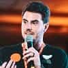 Foto Fellipe com um microfone na mão dando uma palestra