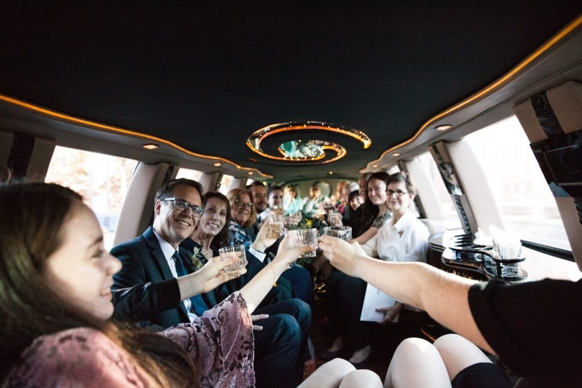fun wedding in a limo where they're enjoying the event process