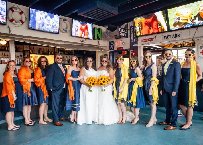 Happy brides at their wedding with their bridal party
