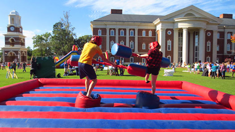 Two pre-teens playing inflatable joust at party