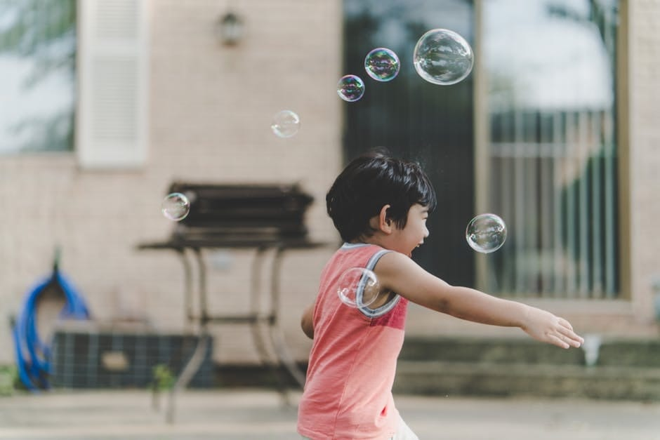 Kid blowing bubbles at an outdoor bbq event