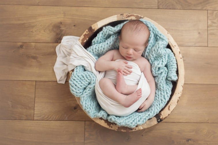 newborn baby photo partially swaddled in a prop basket