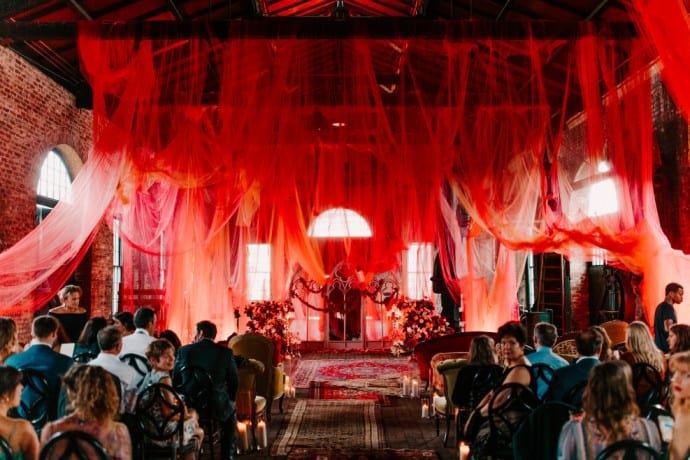 Wedding with red sheer draping and vintage carpet