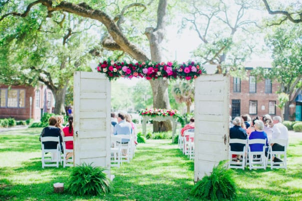 Beautiful outdoor wedding with white chairs and a floral arch.