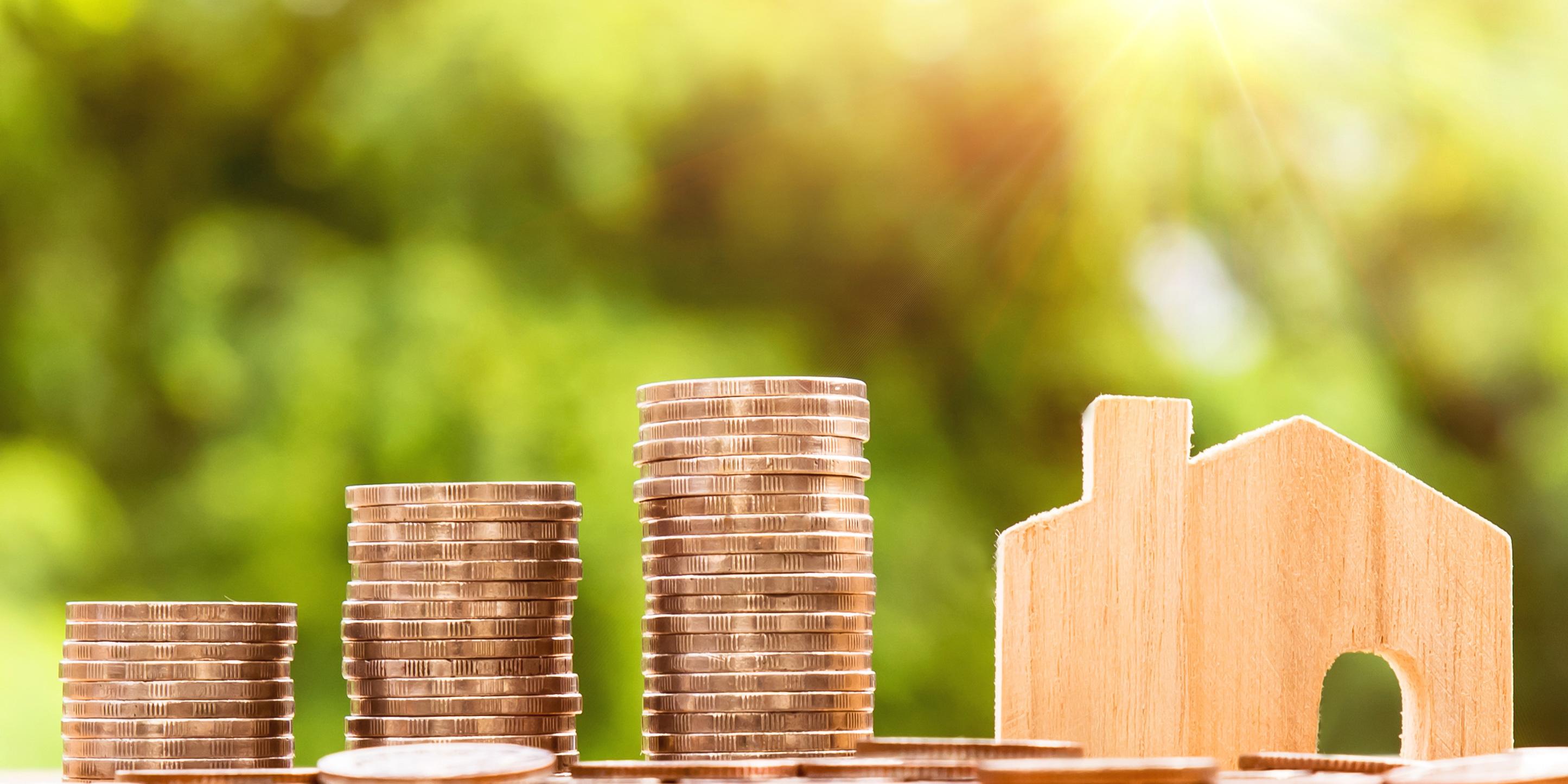 Münzgeld und ein Spielzeughaus