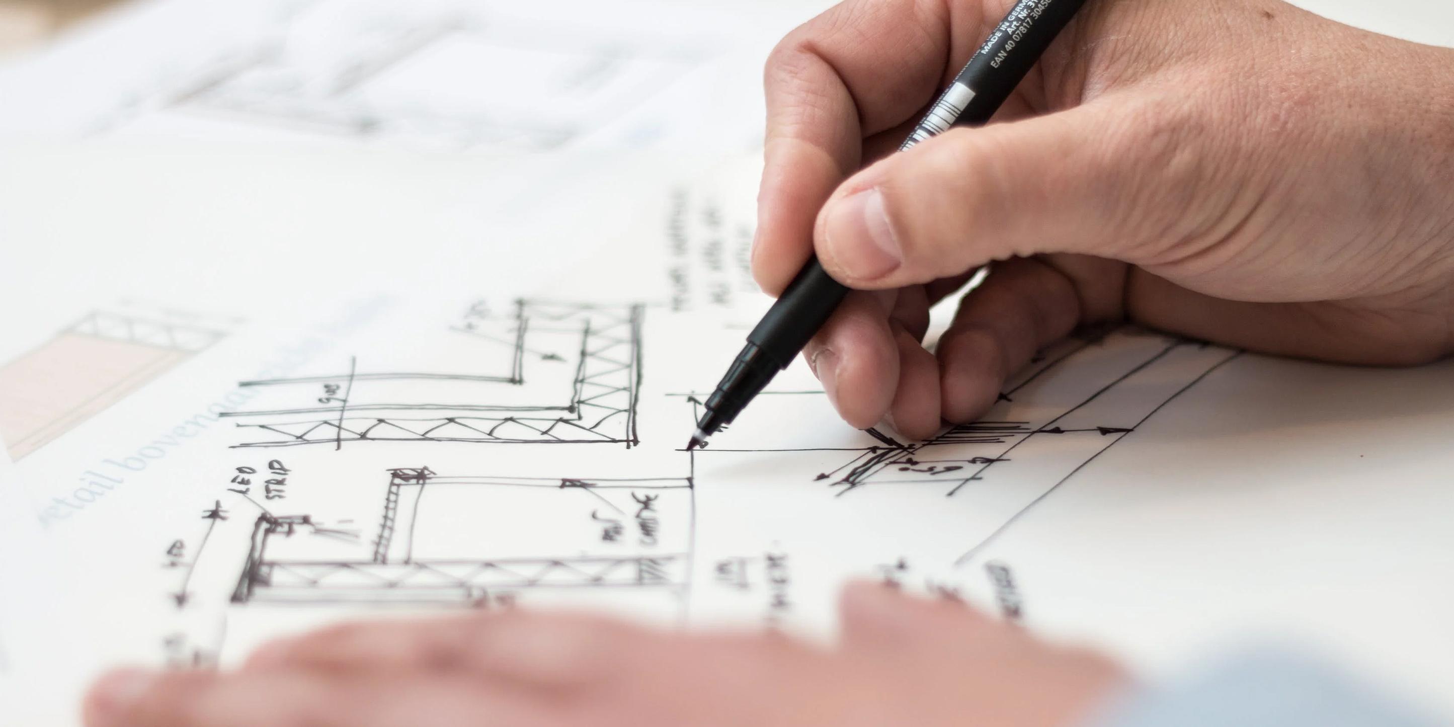 Die Hand eines Mannes zeichnet einen Plan mit schwarzem Fineliner.