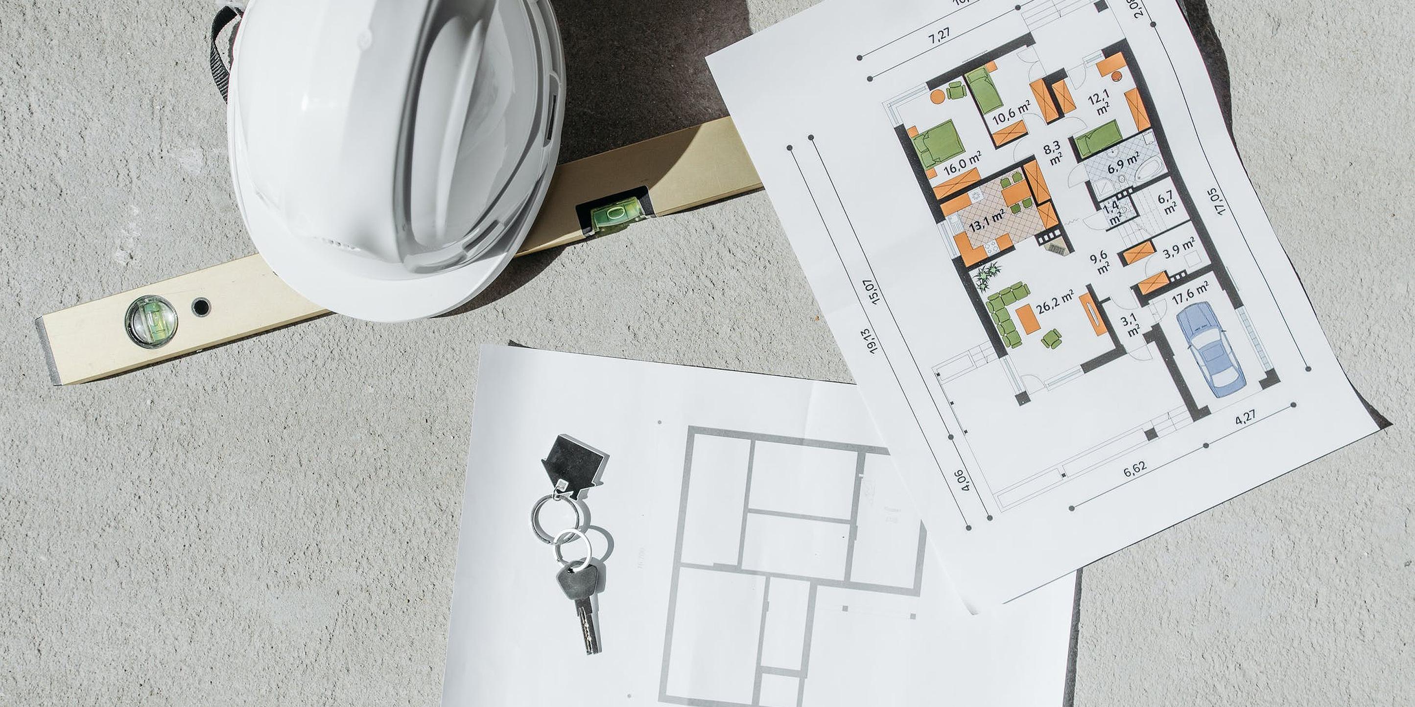 Man sieht einen Grundriss, eine Wasserwaage, einen Bauhelm und einen Schlüssel mit Schlüsselanhänger in Form eines Hauses.