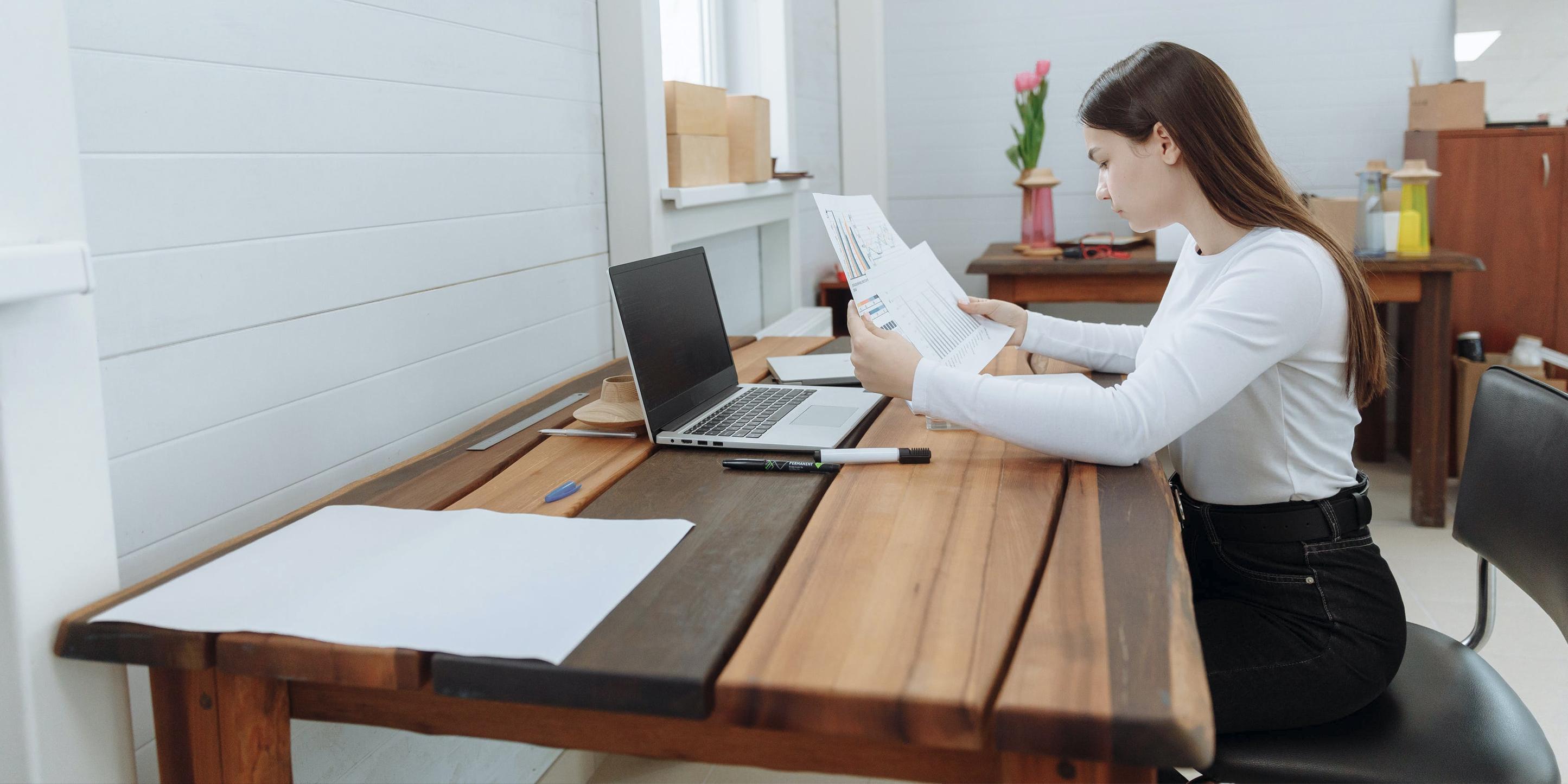 Eine junge Frau sitzt an einem Tisch und blickt auf Dokumente. Diese zeigen verschiedene Diagramme.
