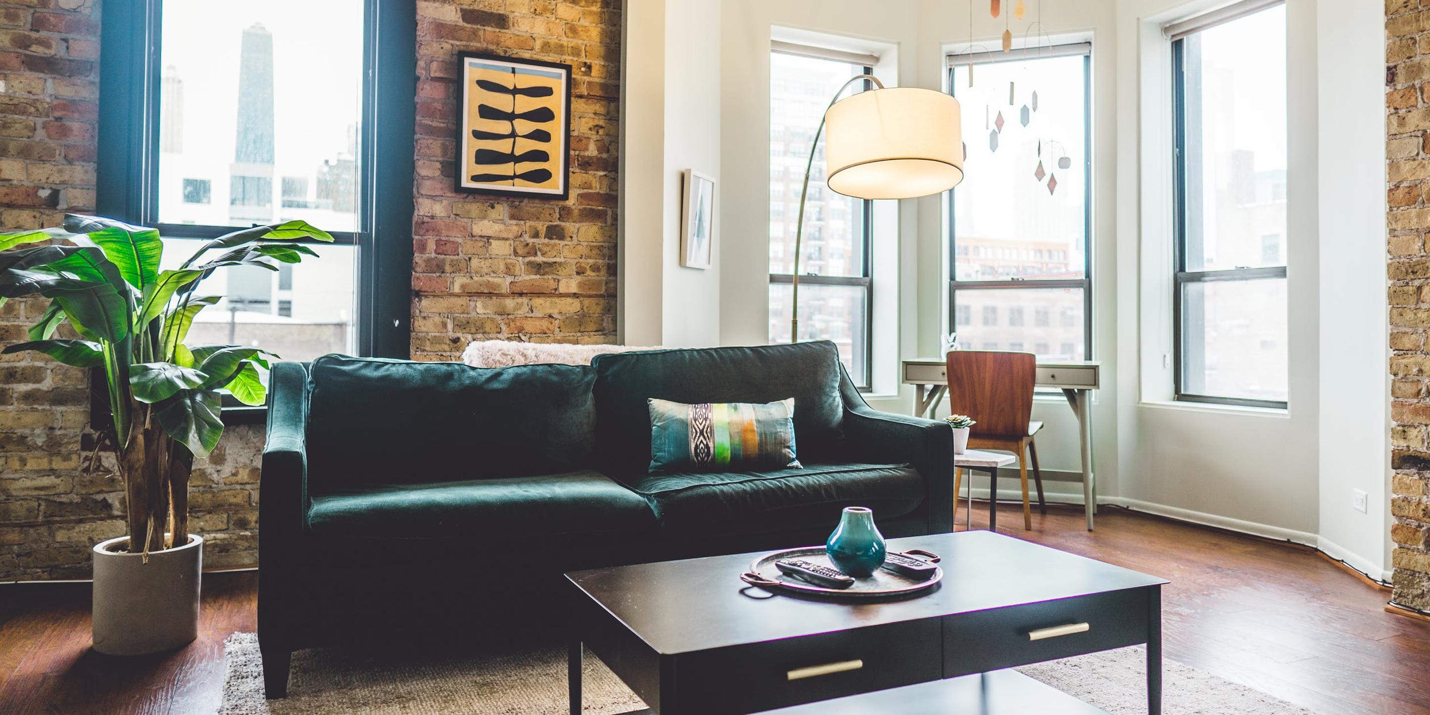 Ein Wohnzimmer: Ein grünes Sofa steht vor einer Backsteinwand. Vor dem Fenster steht ein Schreibtisch.