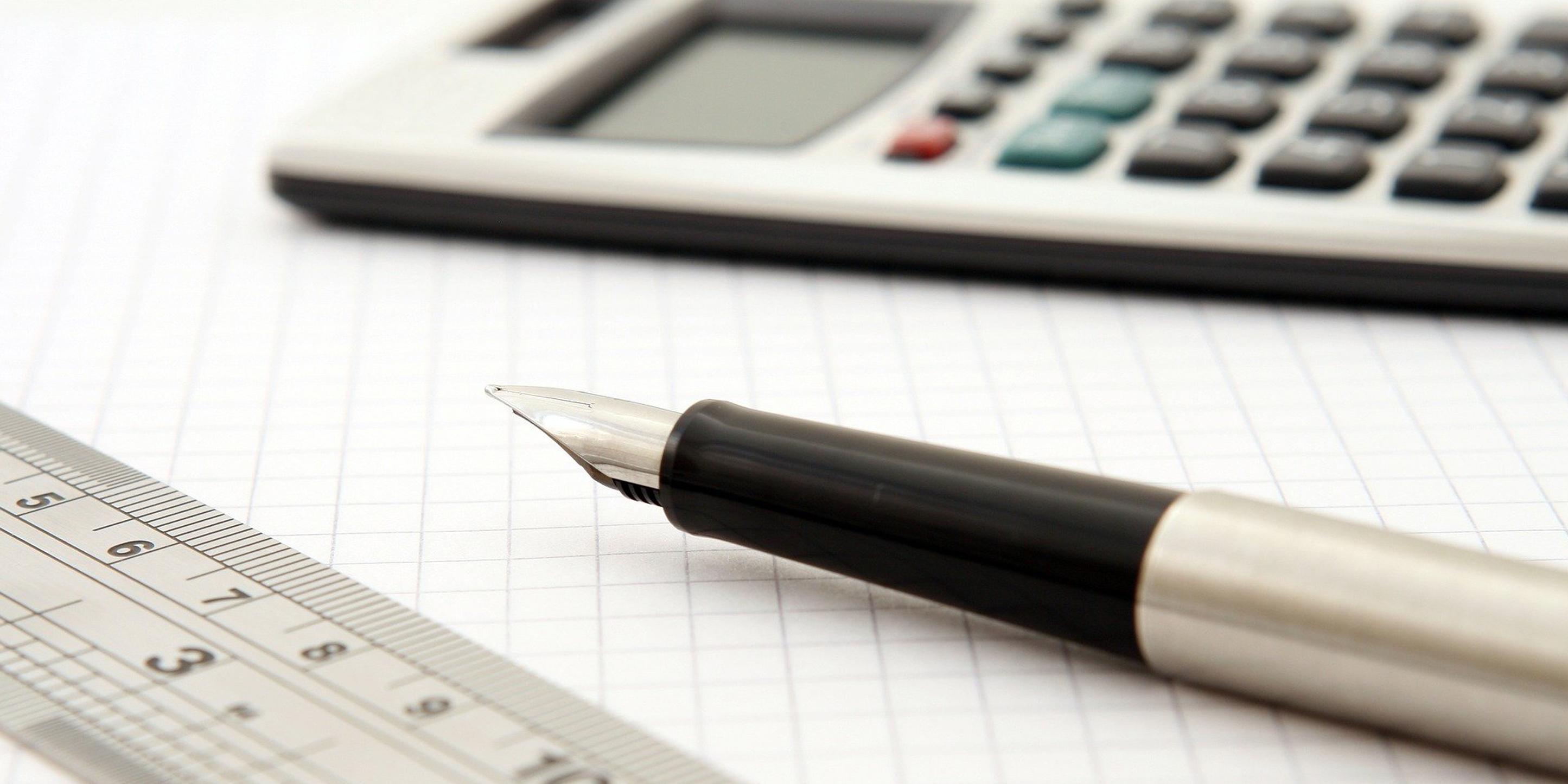 Auf einem karierten Blatt Papier liegen ein Taschenrechner, ein Lineal und ein Füllfederhalter.