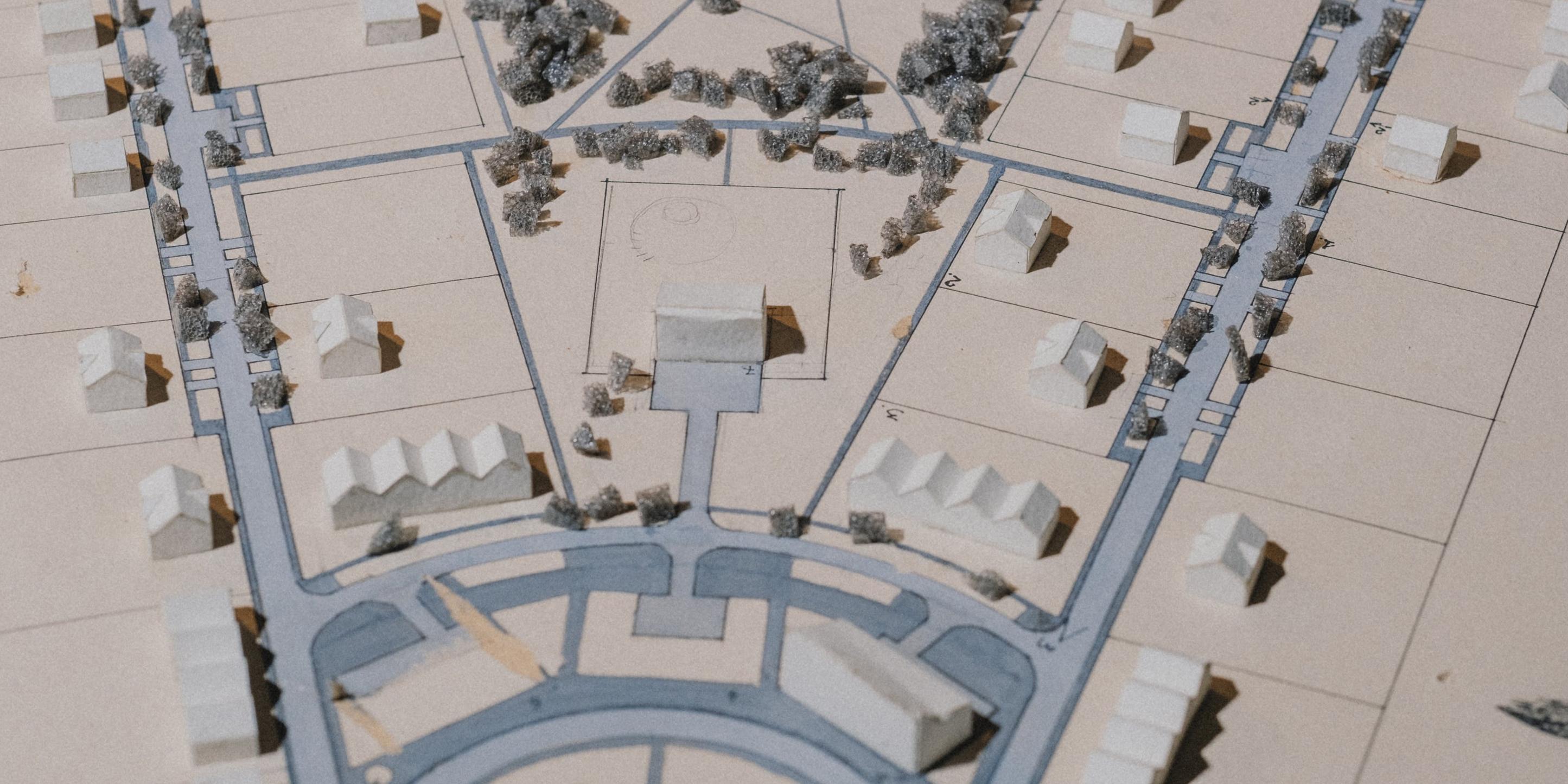 Auf einem Blatt Papier sind Gebiete und Straßen eingezeichnet. Darauf stehen kleine Modellhäuser.