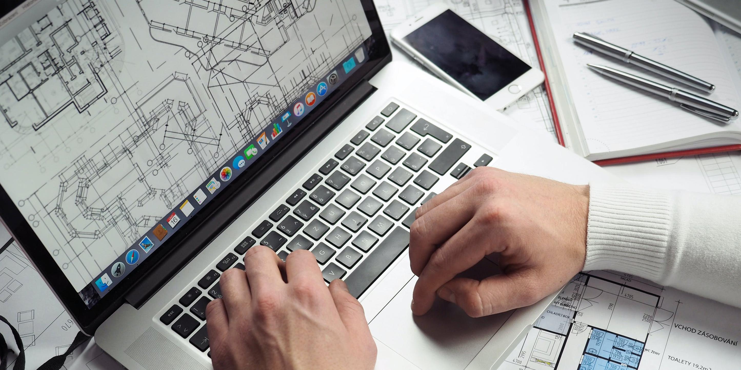Ein Mann sitzt vor einem Laptop, auf dessen Bildschirm ein Grundriss zu sehen ist.
