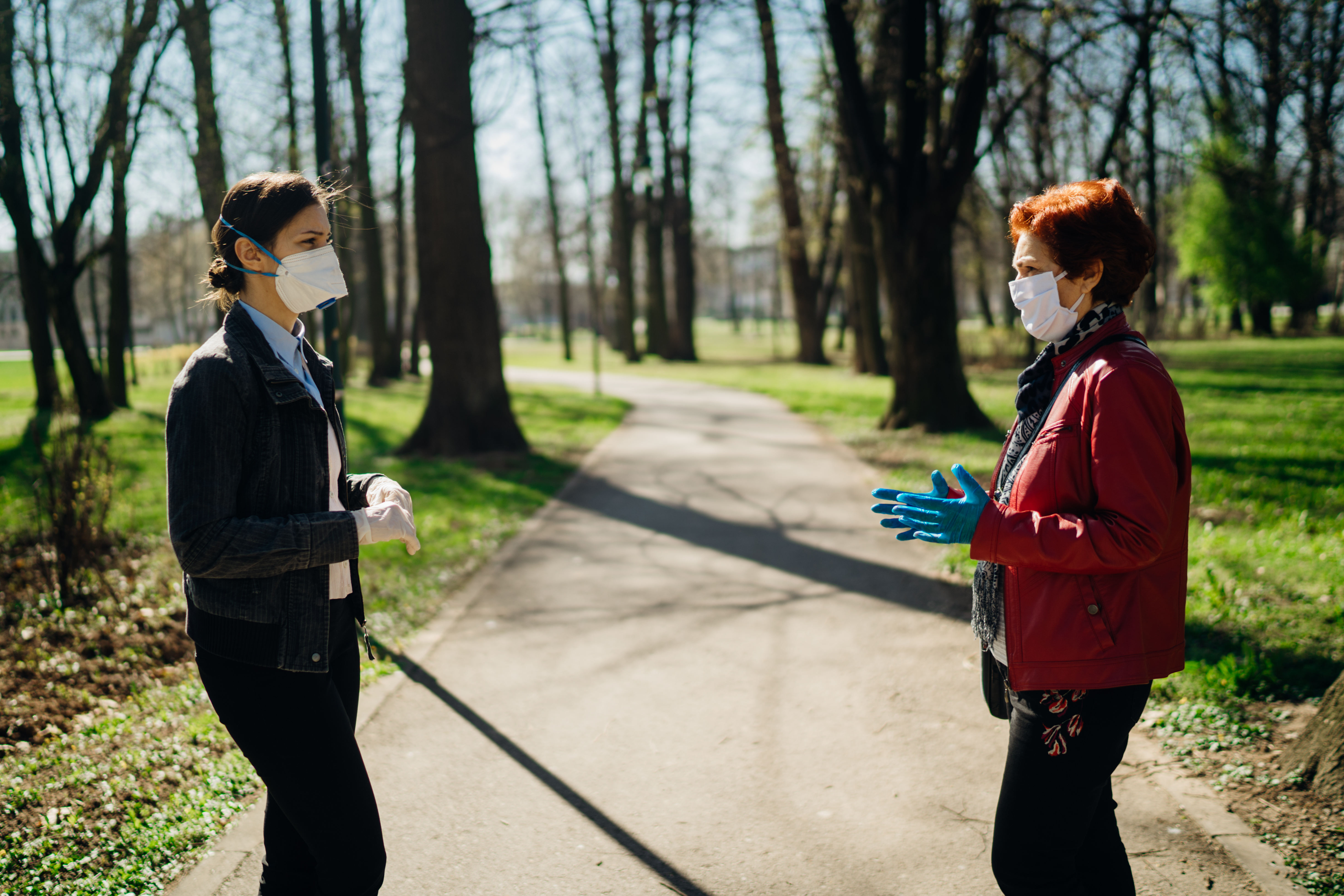 two women in masks engaged in small talk