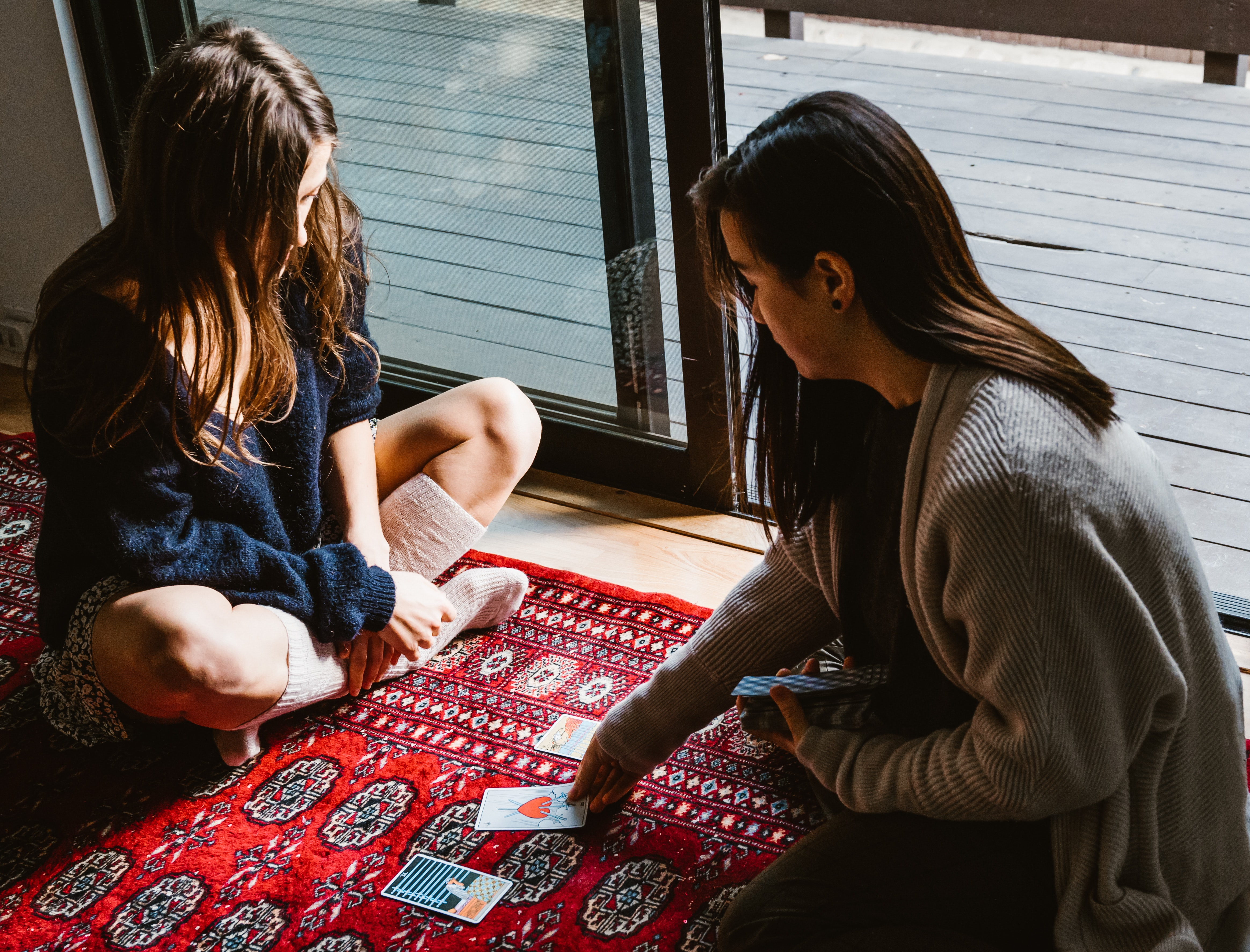 Two Girls Doing Card Reading Sitting On The Floor Gorilla Jobs Blog Tips To Build Strong Relationships with Recruiters