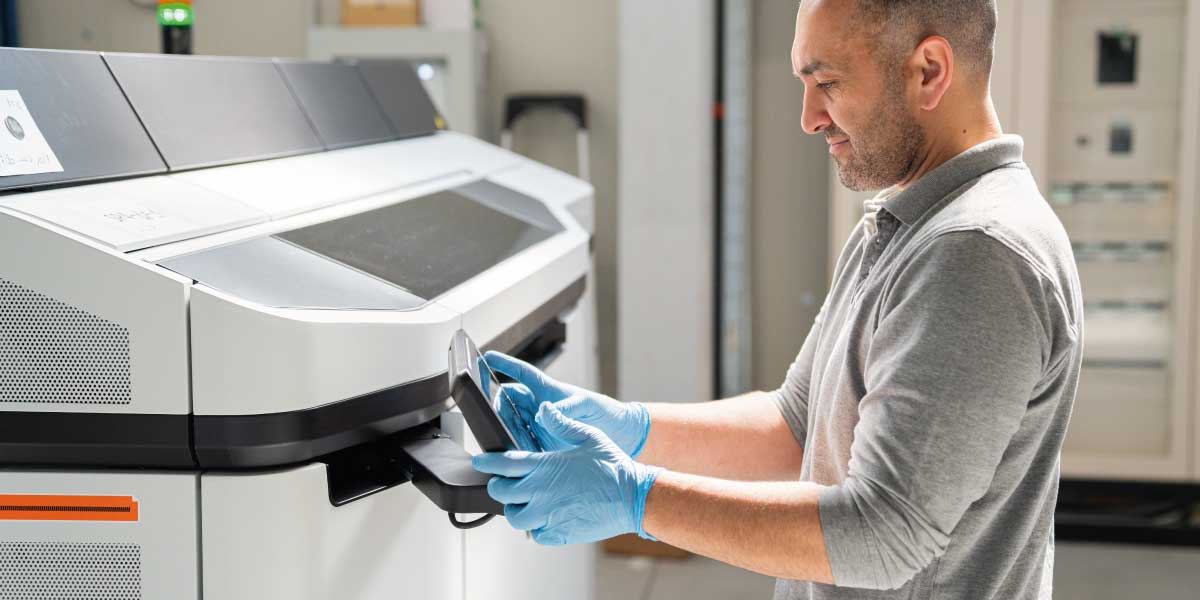 A man operates a 3d printing machine